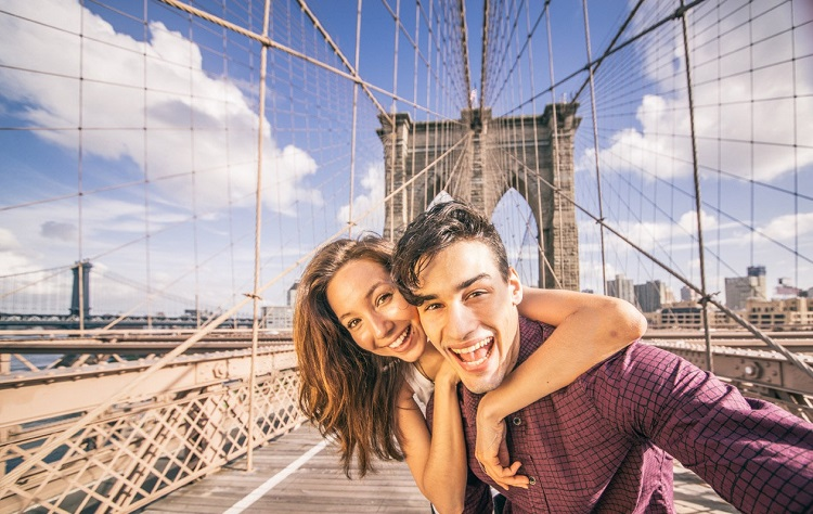 a smiling couple takes a selfie looking down a bridge