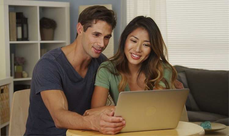 a couple happily researching on their laptop together