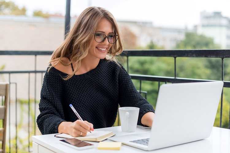 a smiling woman reviewing her credit report online