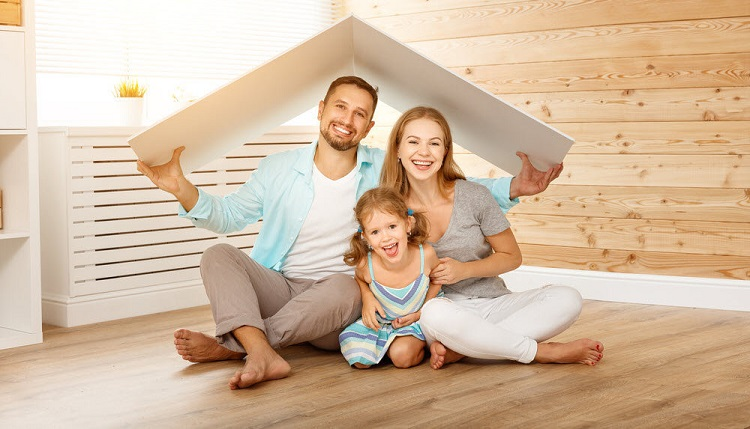 a smiling family holding a roof over their head