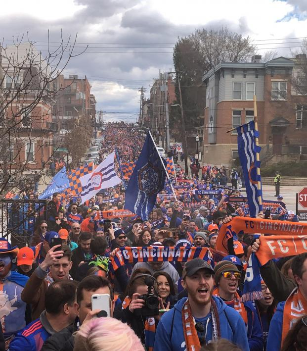 a crowd of FC Cincinnati soccer fans marching towards the stadium to attend a match