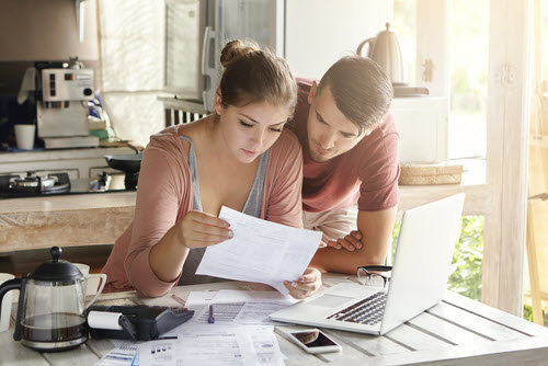 a couple reviewing their finances in their kitchen