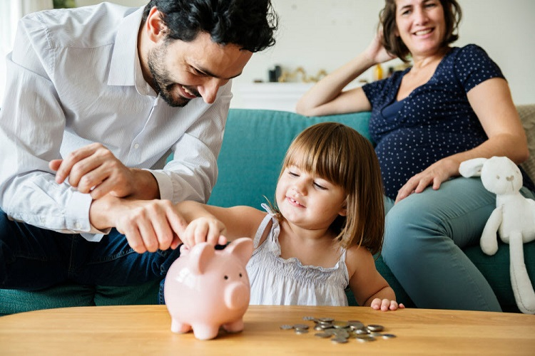 a mother and father help their child store change in their piggy bank