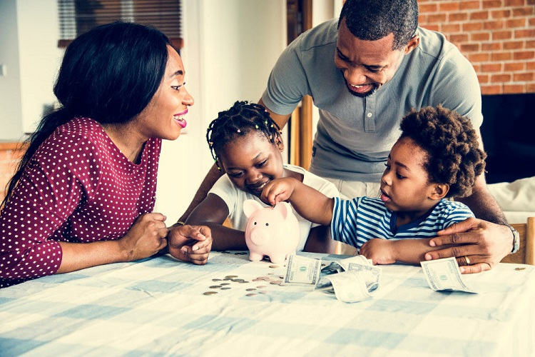 a mother and father help their two children store money in their piggy bank