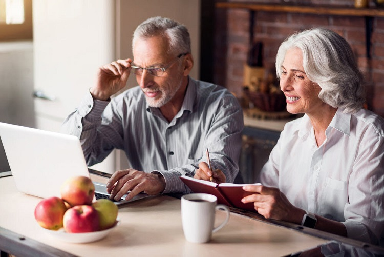 a retired couple sits together, reviewing their finances